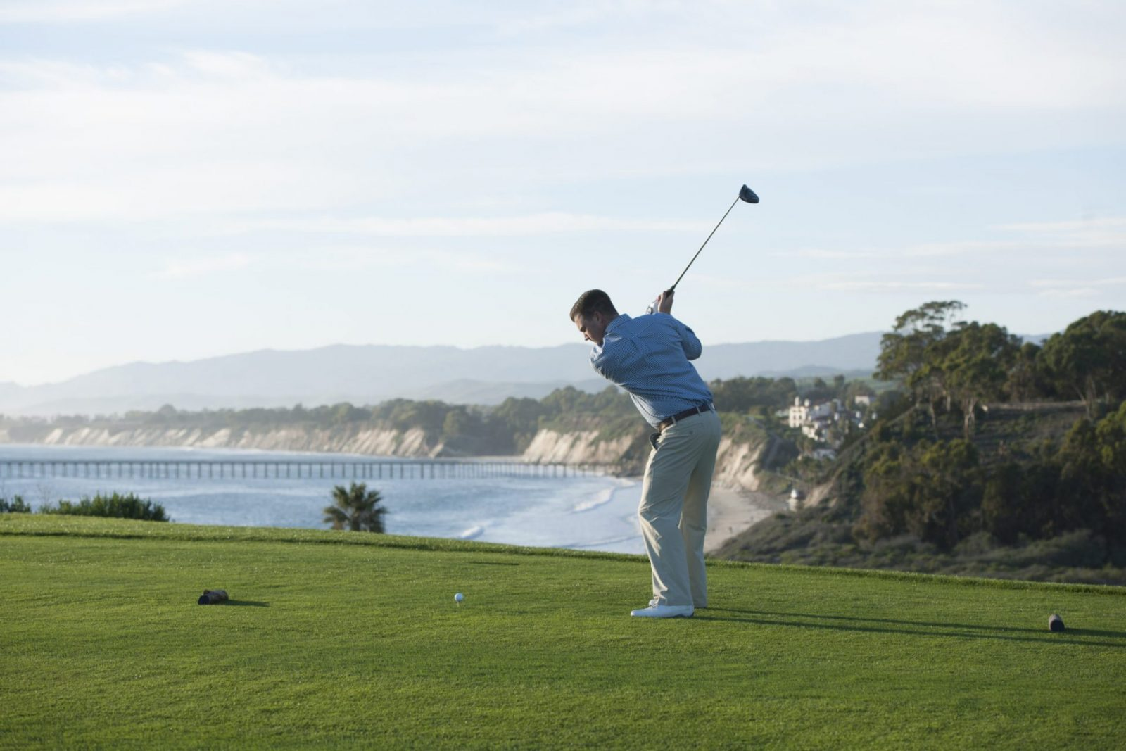 A man golfs at the Sandpiper golf club, with the ocean in the distance.