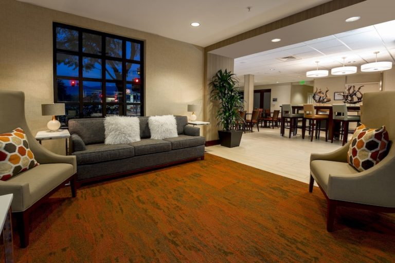 Hampton Inn Suites Lobby with a couch plush chairs and folliage