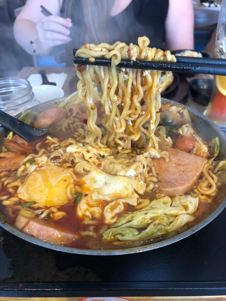Ramen held by chopsticks over large plate of food