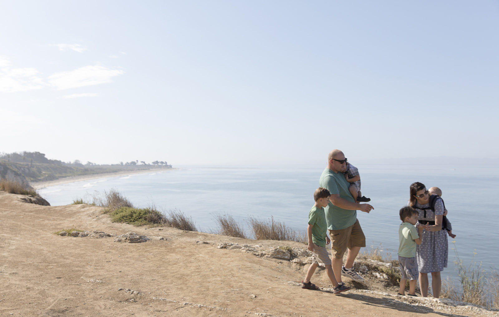 Family of five walking along the coast at Ellwood Mesa