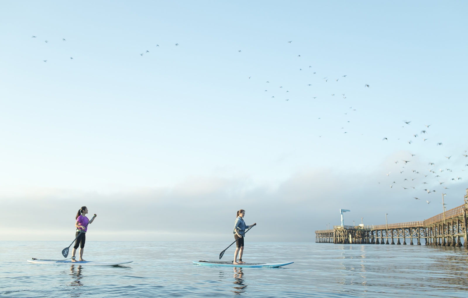 Two girls paddle boarding next to the Goleta Pier