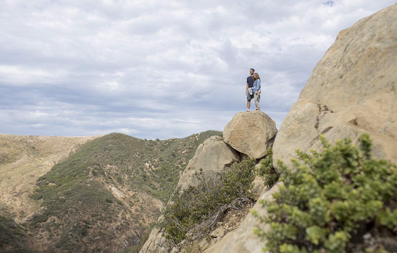 Couple standing on top of a boulder overlooking Gaviota State Park