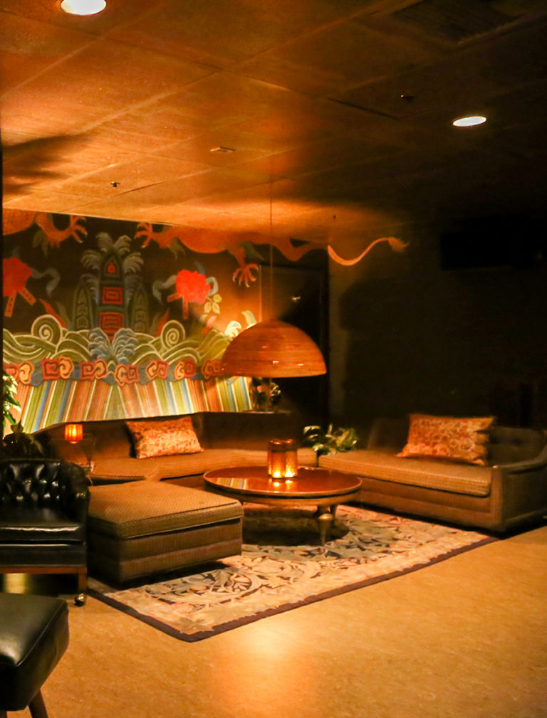 Intimate space with couch, coffee table and a mural on the wall
