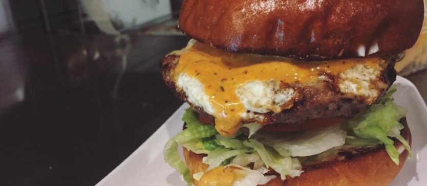 Image of a large burger with an egg topping and coleslaw at Kahuna Grill in Goleta.