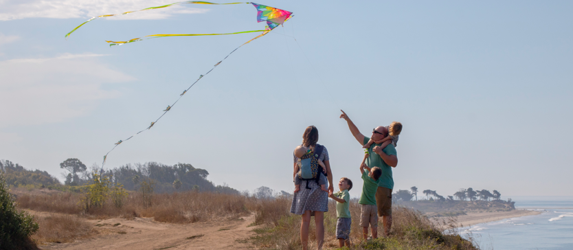 Family of five flying a kite on a hiking trail overlooking the ocean.