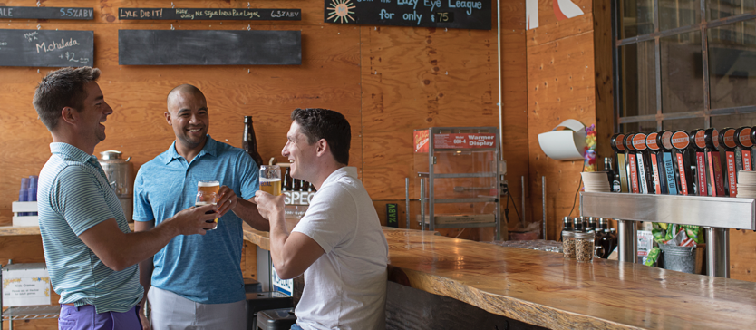 Three guys sharing conversation and beer at M Special Brewery in Goleta