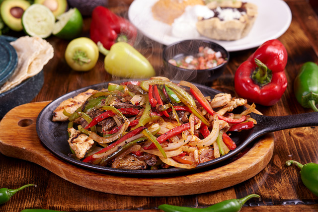 Fresh fajitas surrounded by peppers and salsa at Los Arroyos Mexican Restaurant