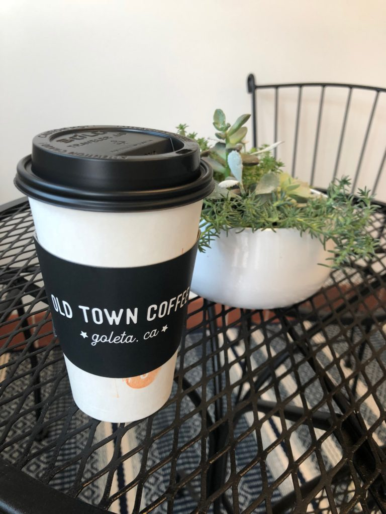 Old Town paper coffee cup and centerpiece plant on metal table