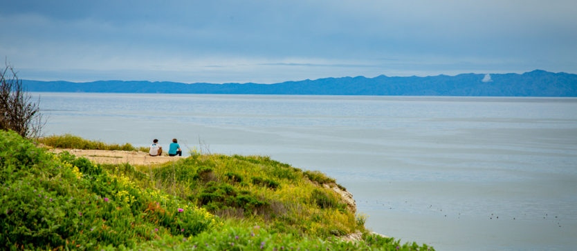 Two people sitting on a bluff overlooking the ocean
