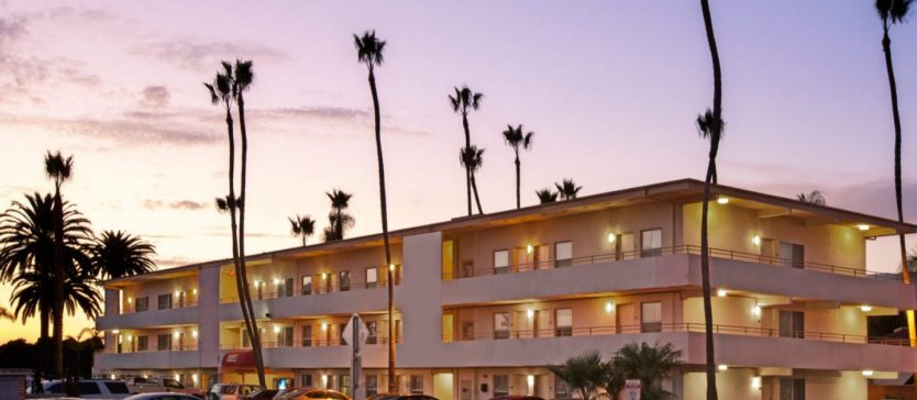 A photo of the Super 8 Motel in Goleta, California framed by tall palm trees beneath a violet sunset.