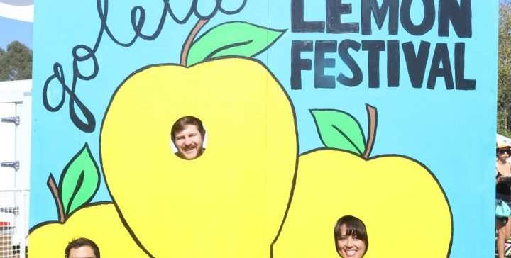 An illustrated sign (green, sky blue, yellow) with smiling faces peering through holes in the depicted lemons.